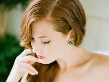 Auburn hair bride portrai with emerald earrings and red lipstick