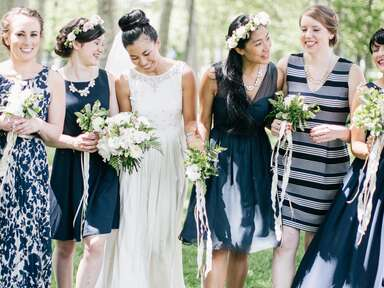 Bride with bridesmaids in mismatched navy blue, striped and patterned bridesmaid dresses