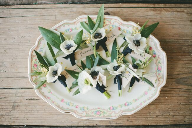 Honey & Poppies created simple, modern boutonnieres with white anemones and olive leaves for Brendon and his groomsmen to wear with their classic black suits. For a subtle hit of color and to tie in with the wedding's palette, the boutonnieres were accented with short lengths of navy ribbon.