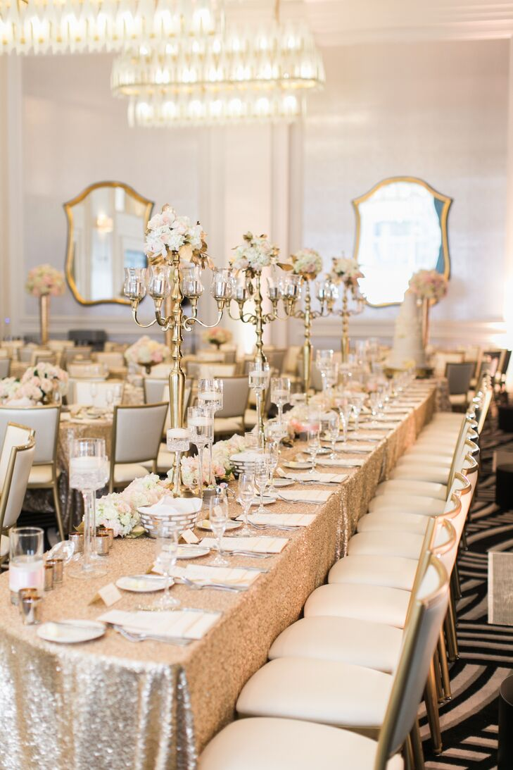 The bridal party's reception table featured four gold candelabras with small floral arrangements atop. Glass vases were filled with floating candles.