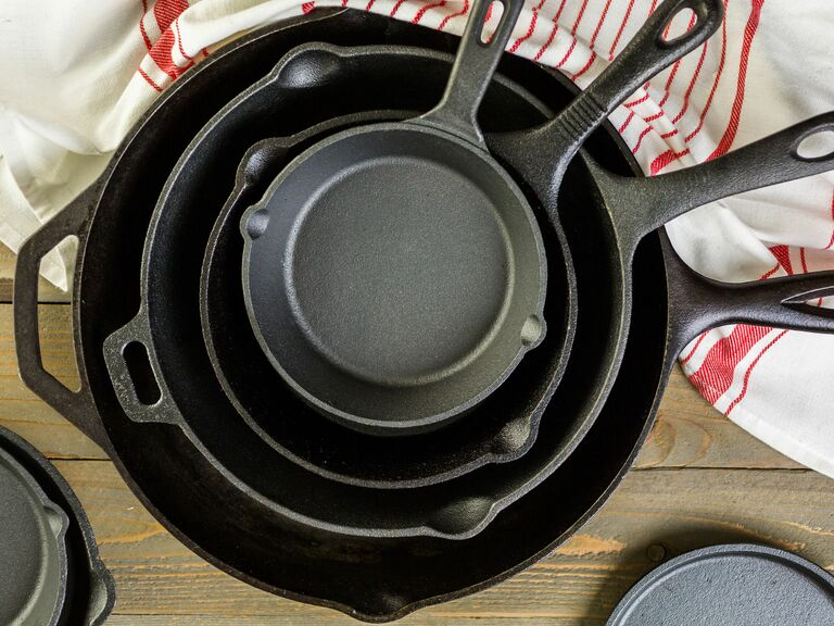 cast iron pans stacked on wood table next to dish towel