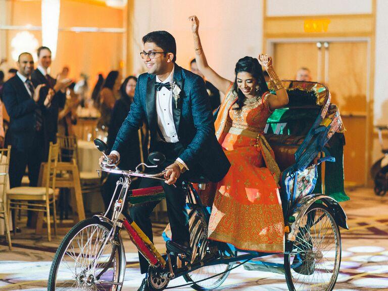 Bride and groom entering wedding reception on bike