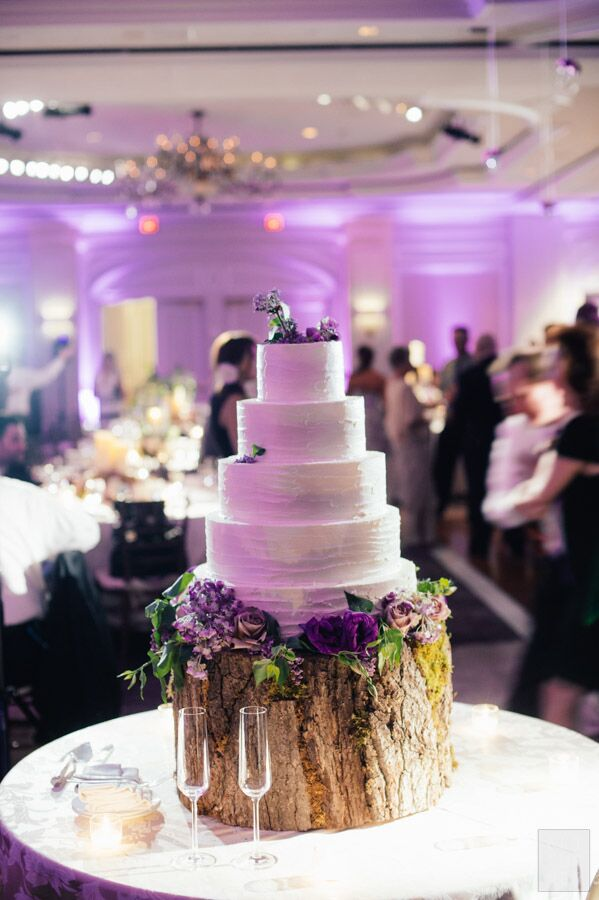 The five tier, white wedding cake was decorated with purple and white flowers and presented on a rustic wood slab.