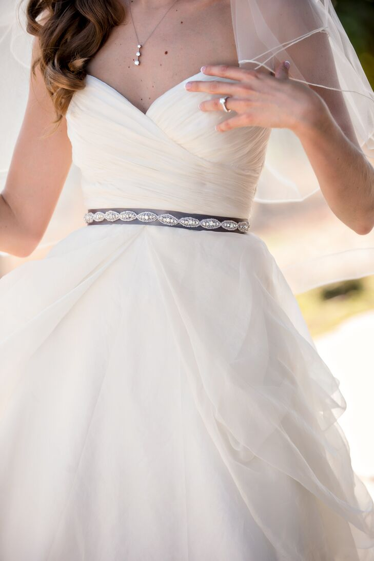 """""""Keeping within the theme of customizing everything, I found a dress I loved and then created a gray ribbon belt with crystals to go with it,"""" explains the bride."""