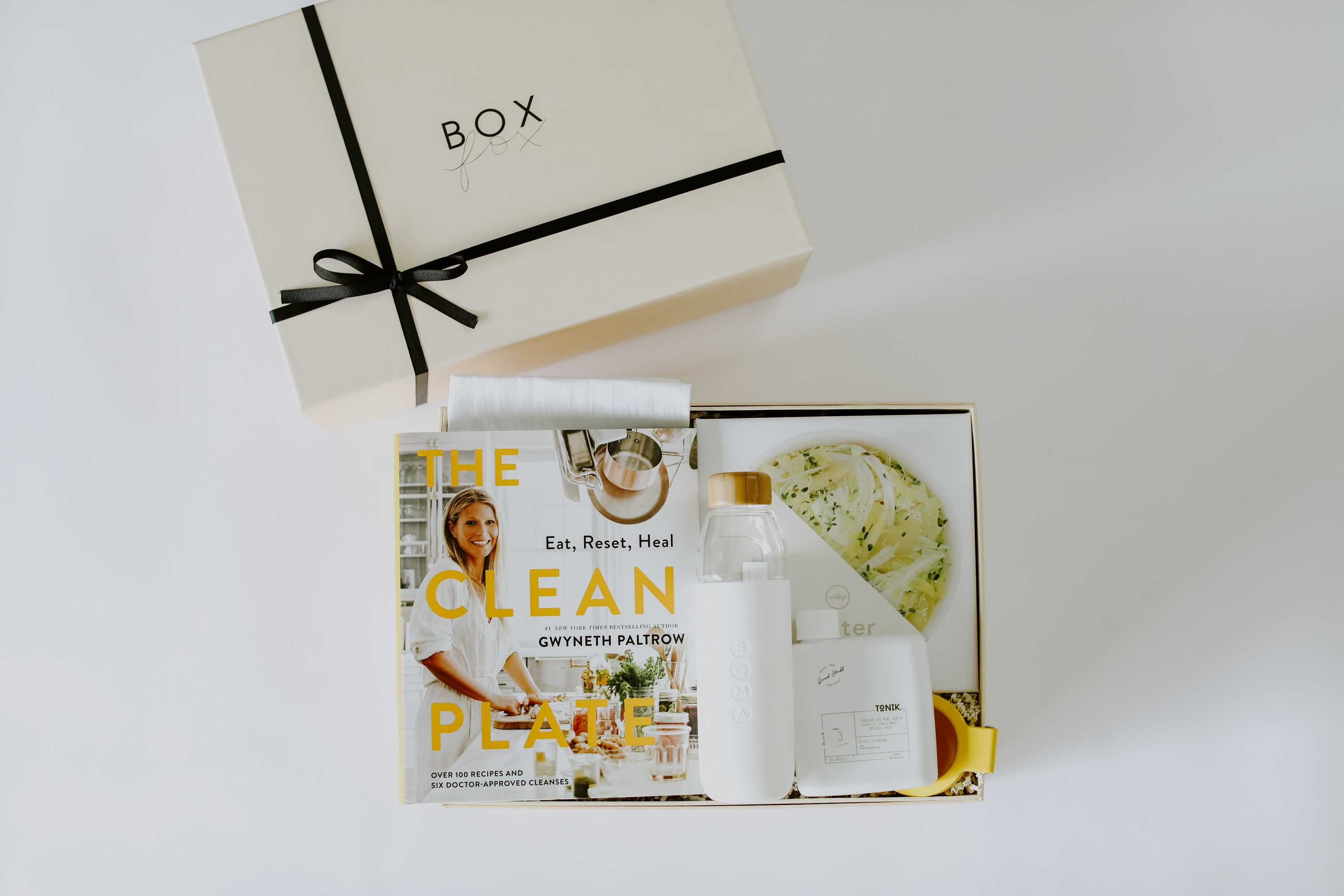Well-packed gift box with a cookbook, salad plate and water bottle for mother's day gift