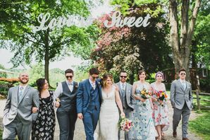 Whimsical Wedding Party in Mismatched Summery Attire Posed Below Sign Hanging in Trees