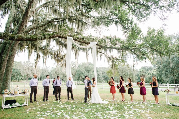 Their aisle decor couldn't have been more chic. Ivory skeleton magnolia leaves cascaded down the aisle and filled their ceremony space by an ivory fabric wedding arch.