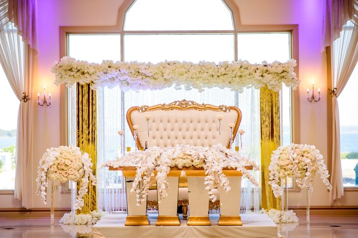 Nkenna and Ekwere pulled out all the stops for the reception at Greentree Country Club in New Rochelle, New York. To ensure a few private moments, the couple opted for a sweetheart table—complete with an opulent gilded settee—which they adorned with arrangements of cascading ivory orchids. A gold arch decked out in full white blooms hung overhead, amplifying the vignette's luxe look.
