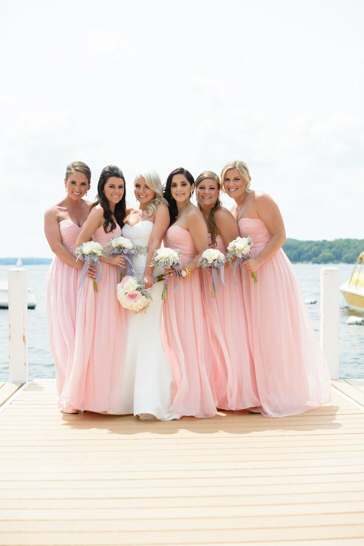 The bridesmaids accented their blush Donna Morgan dresses with white peony bouquets wrapped with black-and-white-striped ribbon.
