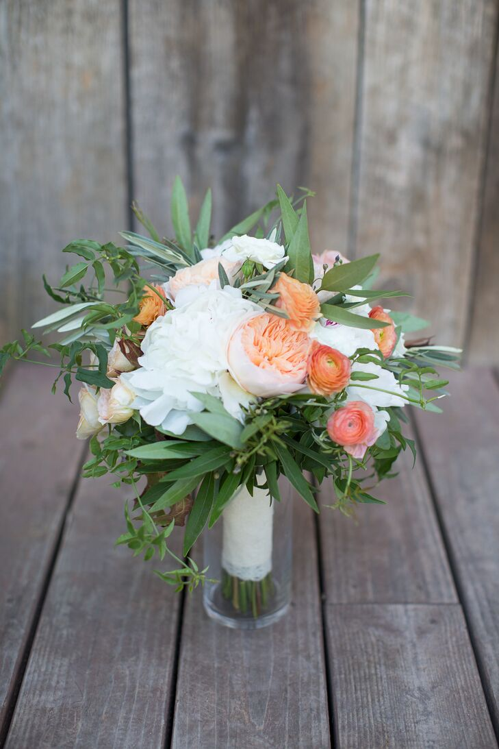 To add a touch of color to her bridal look, Natalie Galasso Designs added coral and peach-colored garden roses and ranunculuses to Mariellen's textured bouquet. Full white peonies and olive leaves introduced texture and drama to the arrangement.