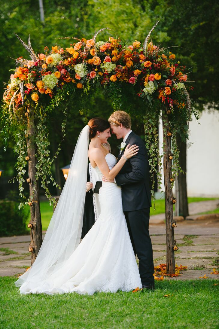 Taylor and his father built the wedding arch using wood from the family ranch. Vibrant roses, dahlias, hypericum berries, hydrangeas and pheasant feathers sprung out of the top, with trails of cascading ivy and fall foliage to complete the design.