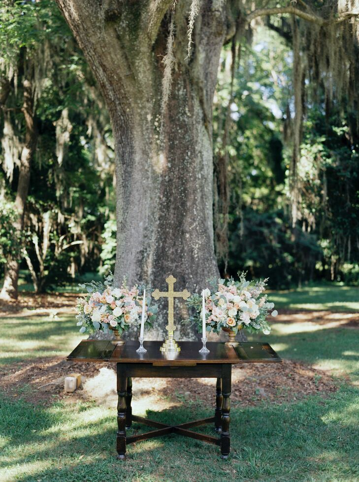 """A cherrywood table with twin white candlesticks and a gold cross formed the altar at their Christian-based ceremony. Romantic arrangements of eucalyptus and roses decorated both sides. """"Our goal was to keep the ceremony decor simple, so everyone could focus on the message,"""" Laurie says."""
