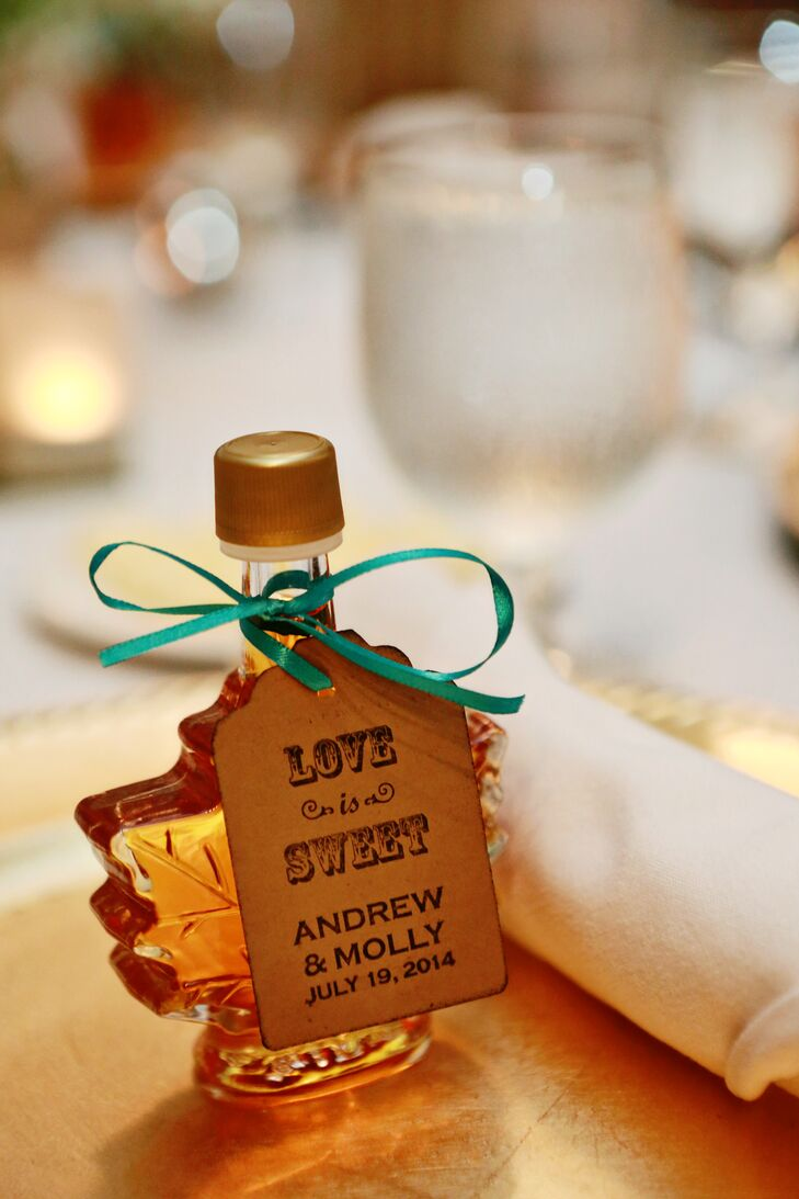 """As a nod to Andrew's Canadian nationality, he and Molly gave their guests maple-leaf-shaped  bottles of maple syrup. The bottles were tied with teal ribbon and tags that read """"Love Is Sweet."""""""
