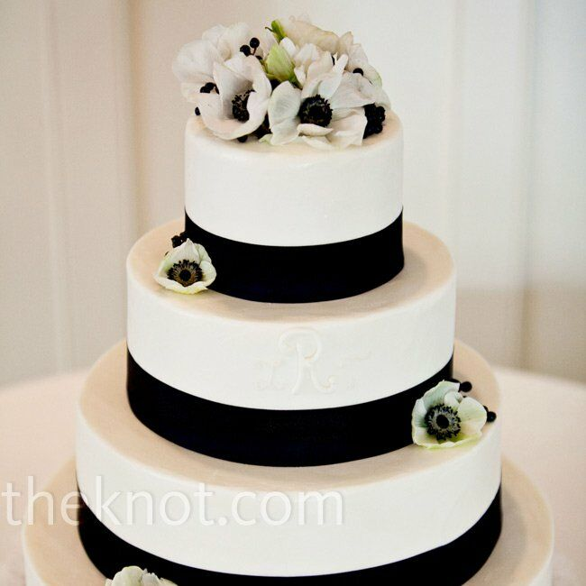 Each tier of the buttercream cake was wrapped in navy grosgrain ribbon. White anemones decorated the tiers and served as a cake topper.