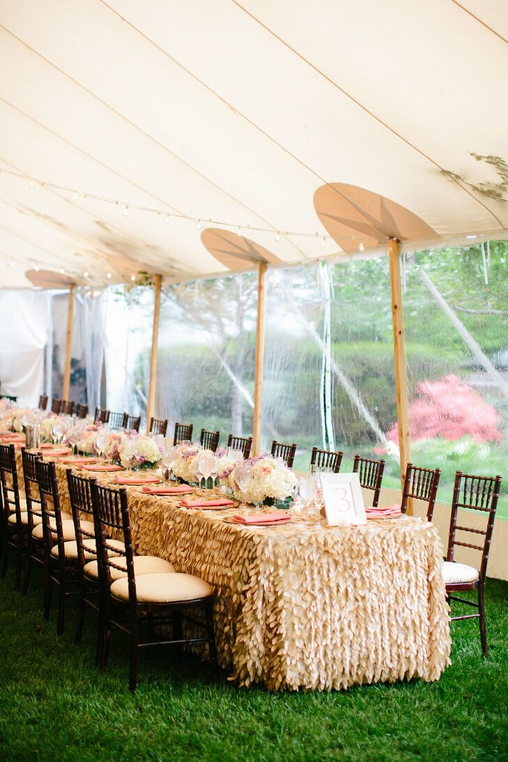 A feather-inspired texture on the gold tablecloths added dimension to the tented reception space.