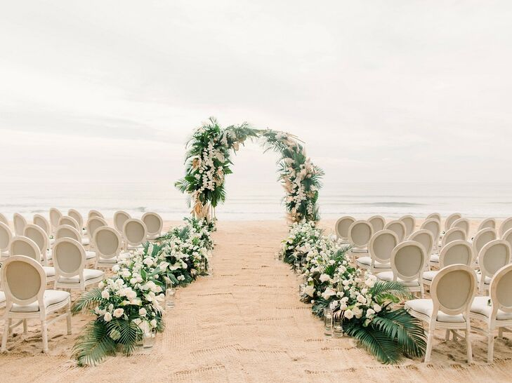 Beach Ceremony Site with Wedding Arch, Tropical Flowers and Palm Leaves