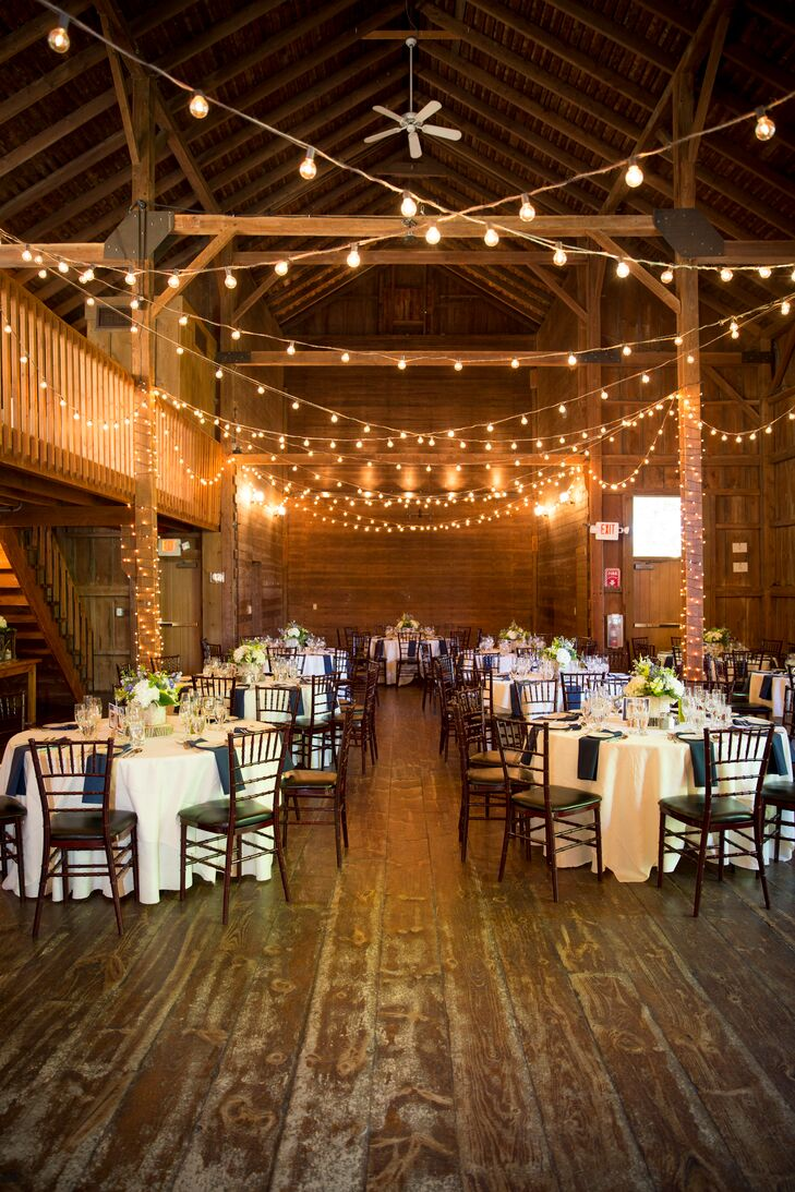 Wanting a wedding with plenty of rustic flair, Tara and Graeme knew a barn would be perfect for their early-summer affair. As a former functioning farm, the Barns at Wesleyan Hills in Middletown, Connecticut, had an authentic feel the pair loved, plus acres of lush rolling hills, a quaint pond and an old willow tree. The barn itself was rich in history and character with its post and beam structure, beautiful wood paneling and distressed wooden floors. Classic white linens and bunches of fresh, white summer blooms introduced a layer of classic elegance, while strings of brightly lit bistro lights provided plenty of warmth and ambiance.