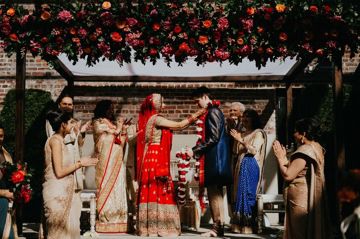 "Following tradition, Anjali and Christophe incorporated a mandaap into their ceremony but with a twist. ""I wanted a rustic and minimalistic look, which is different from most Hindu weddings,"" Anjali says. ""I wanted a simple wooden structure with simple flowers and greenery at the top. It turned out to be a little more elaborate than expected, but it was beautiful."""