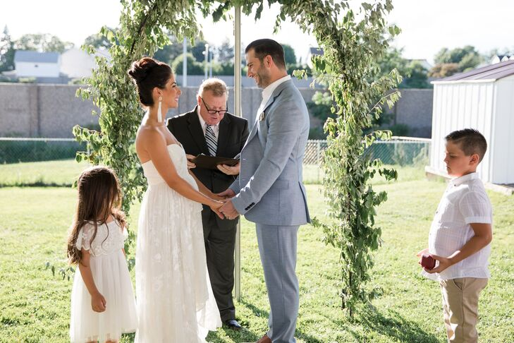 Intimate Backyard Wedding Vows with Greenery Arch