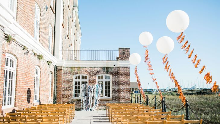 "Charlee-Ann, bride and owner of Fancy Face Studio specializing in wedding decor made her signature tassel garlands in rose gold and strung them from large balloons for the ocean side ceremony. ""Driving to the wedding over the bridge in Charleston, I could see the mylar garlands glistening in the sunshine and I was overwhelmed with joy"", she recalls."