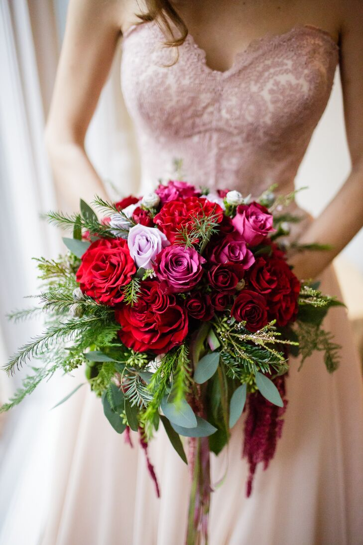 Her bouquet was fit for an enchanted garden. Designed by Judy Suarez, their florist, pink and red roses and red peonies were surrounded by lush greenery. Eucalyptus and leaves from an evergreen tree brought in their natural flair.