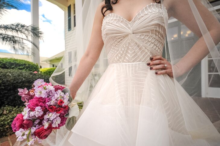Juliana chose a strapless modern Hayley Paige ball gown with a sweetheart neckline, blush lining, fun geometric pattern and tiered tulle skirt. She paired the look with a floor-length veil and silver hair accessory.