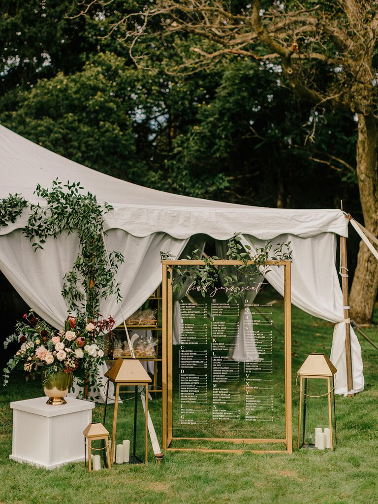 Gold seating chart with candles and lanterns next to white wedding tent