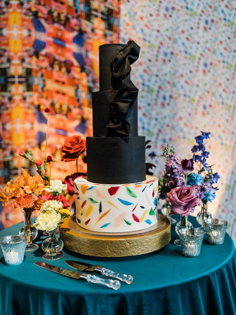 Four-tier wedding cake with three black tiers with fondant ribbon and white base tier with colorful confetti print