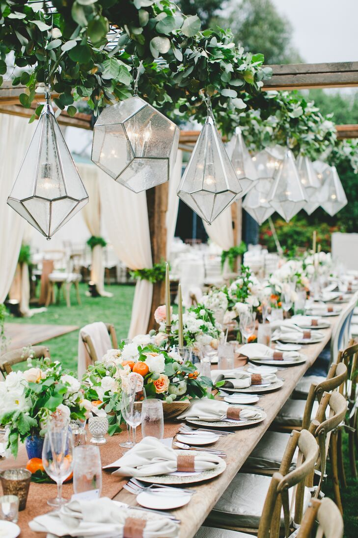 At the outdoor garden reception at Rancho Valencia in Rancho Santa Fe, California, chic geometric chandeliers were strung over the long banquet tables to add light and cozy ambiance.