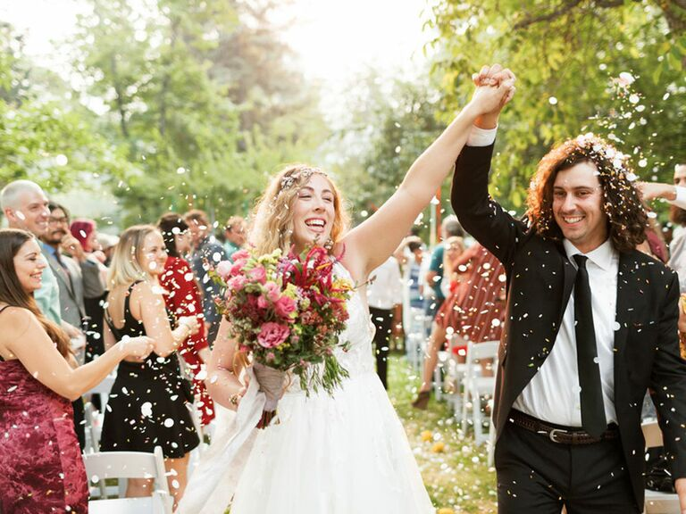 Indie bride and groom walking up the aisle during outdoor forest wedding ceremony
