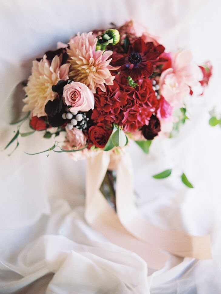 The bride chose a pink and red bouquet that blended roses, peonies and orchids.