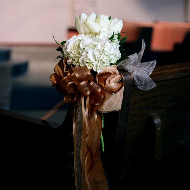 The pews at Andrea and Matt's ceremony were adorned with clusters of white hydrangeas and tulips tied with gold ribbon. I wanted the decor to be simple and not distracting, explains the bride.