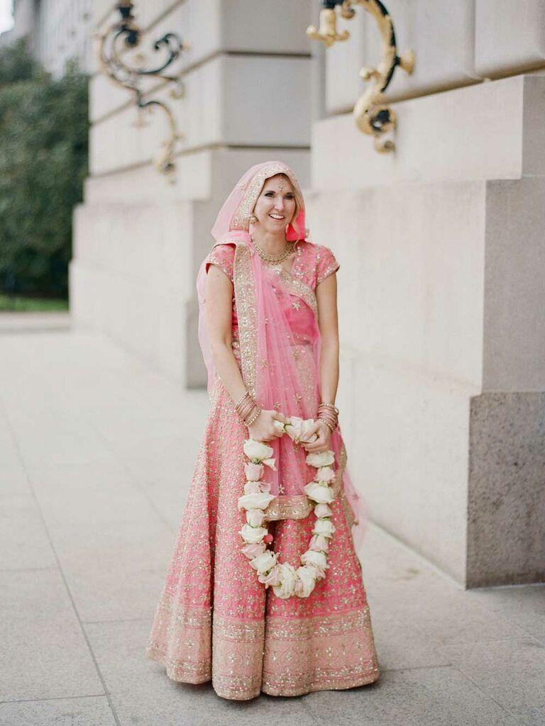 Bride wearing light pink and gold lehenga and saree