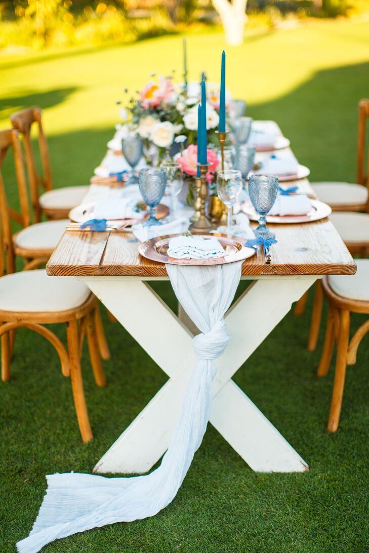 Rustic wooden farm tables and cross-back chairs were arranged in a mango field for the newlyweds' dinner reception at Flora Farm in San Jose del Cabo, Mexico.