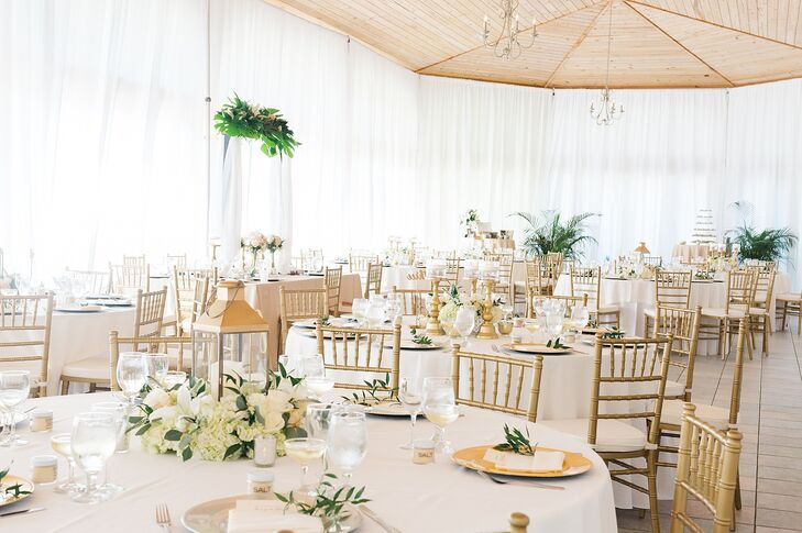 Kay and Ben's reception space at Key Colony Inn in Key Colony Beach, Florida, was decked out in gold and white with gold chiavari chairs and tables cloaked in white linens and topped with lanterns, candles, gold chargers and greenery.