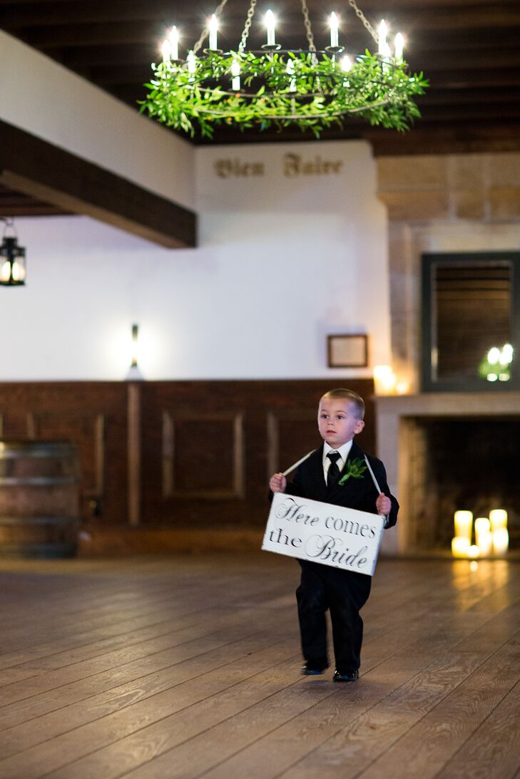 "The ring bearer carried a sign that read ""Here comes the bride"" before Veronica walked down the aisle."