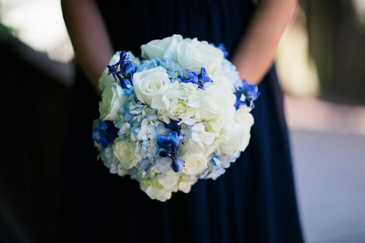 To match the wedding's navy and white palette, the florists at Flowers by Danielle created full bouquets of white and bright blue blooms for the bridesmaids to carry down the aisle. The arrangements were filled with roses, hydrangeas and delphiniums, which popped against the backdrop of the bridesmaid navy dresses.