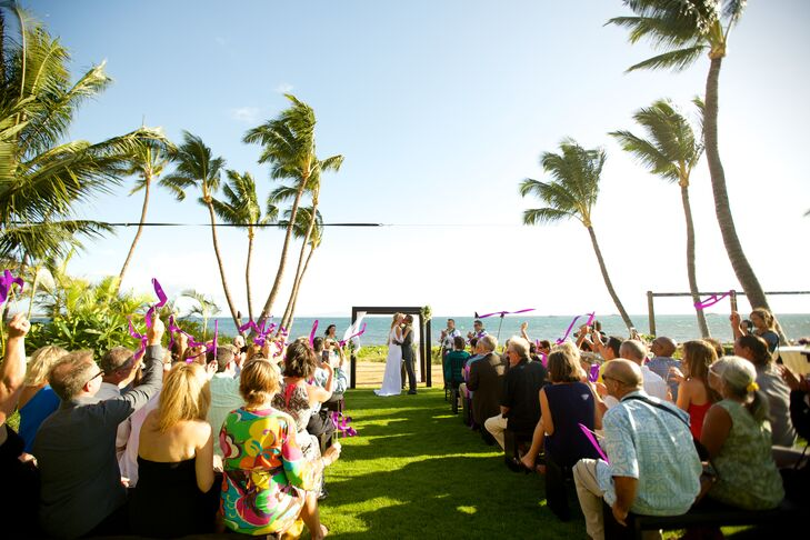 Guests overlooked ocean views with sporadic palm trees during the wedding ceremony outdoors at Sugar Beach Events.