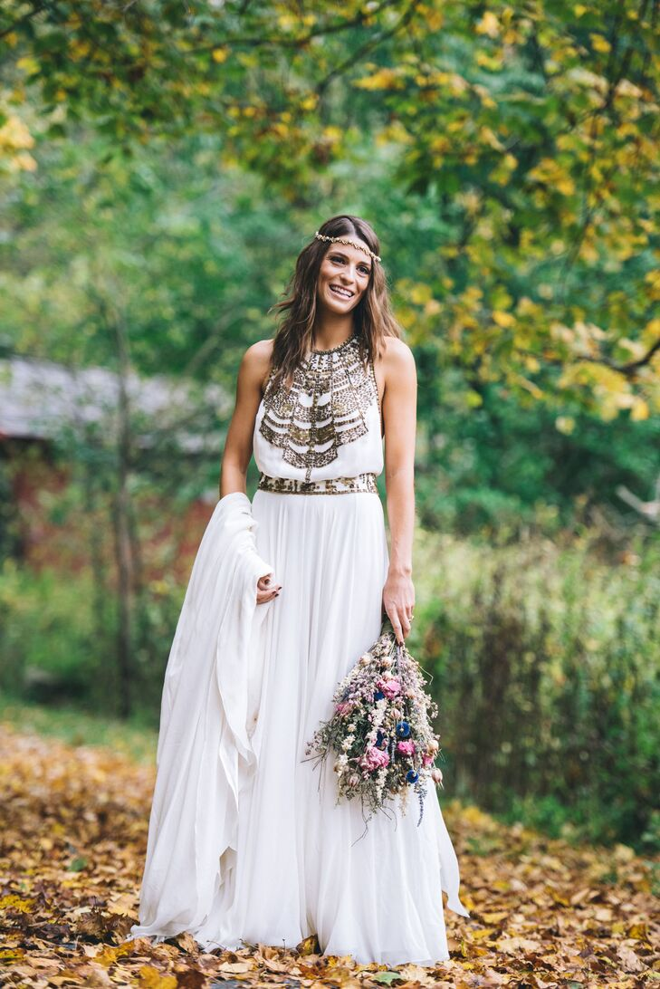 Liza picked out a white wedding dress with the bodice accented in gold geometric shapes with a matching belt. She held her bouquet of dried flowers in her hand.