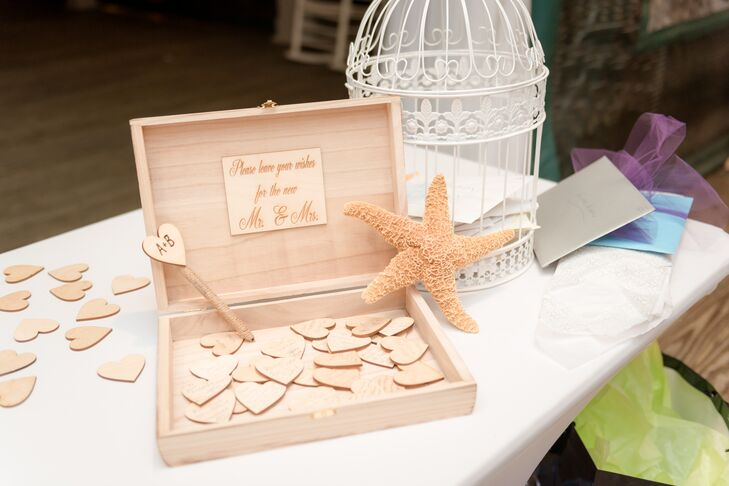 """In lieu of the traditional wedding guest book, Bethany and Ali came up with a different idea. They set out heart-shaped pieces of wood and a wooden chest that read, """"Please leave your wishes for the new Mr. and Mrs."""" They placed it on the gift table next to the card holder for guests to sign at some point during the reception."""