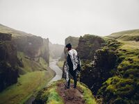 woman standing on green cliff in iceland admiring beautiful mountain scenery