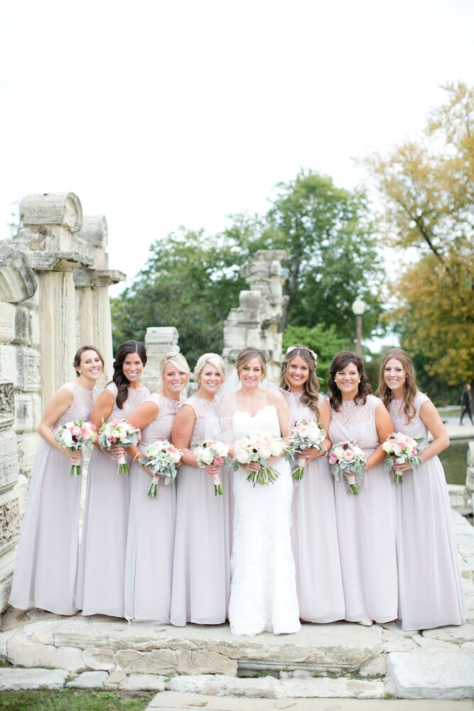 Jessica spent awhile looking for a light blush dress that would work with all her bridesmaids' body types and the boho-chic theme. She found the perfect floor-length, illusion neckline dresses by Jim Hjelm at Hyde Park Bridal in Cincinnati, Ohio. She had each lady complete her look with beaded belts and vintage-style earrings.