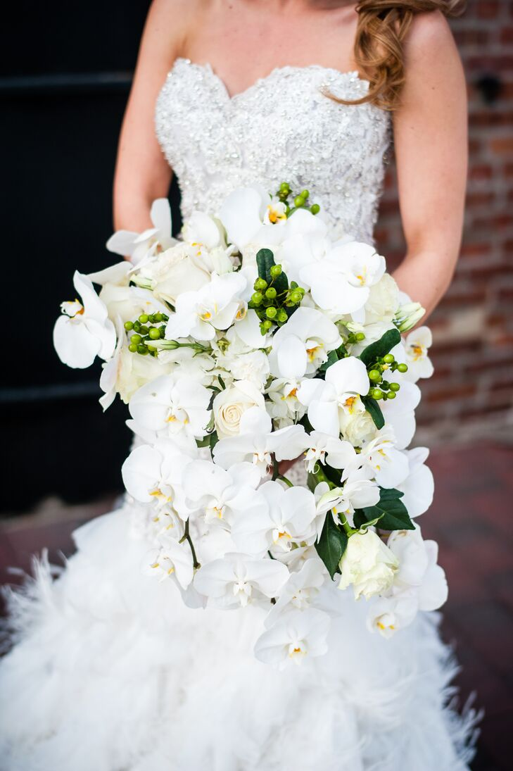 While Hayley's bridal bouquet was classic in color, a bright shade of brilliant white, the standout arrangement was just as stunning as her glam Stephen Yearick dress. Dozens of white orchids, roses and green hypericum berries were gathered into a cascading bundle that was both elegant and modern.