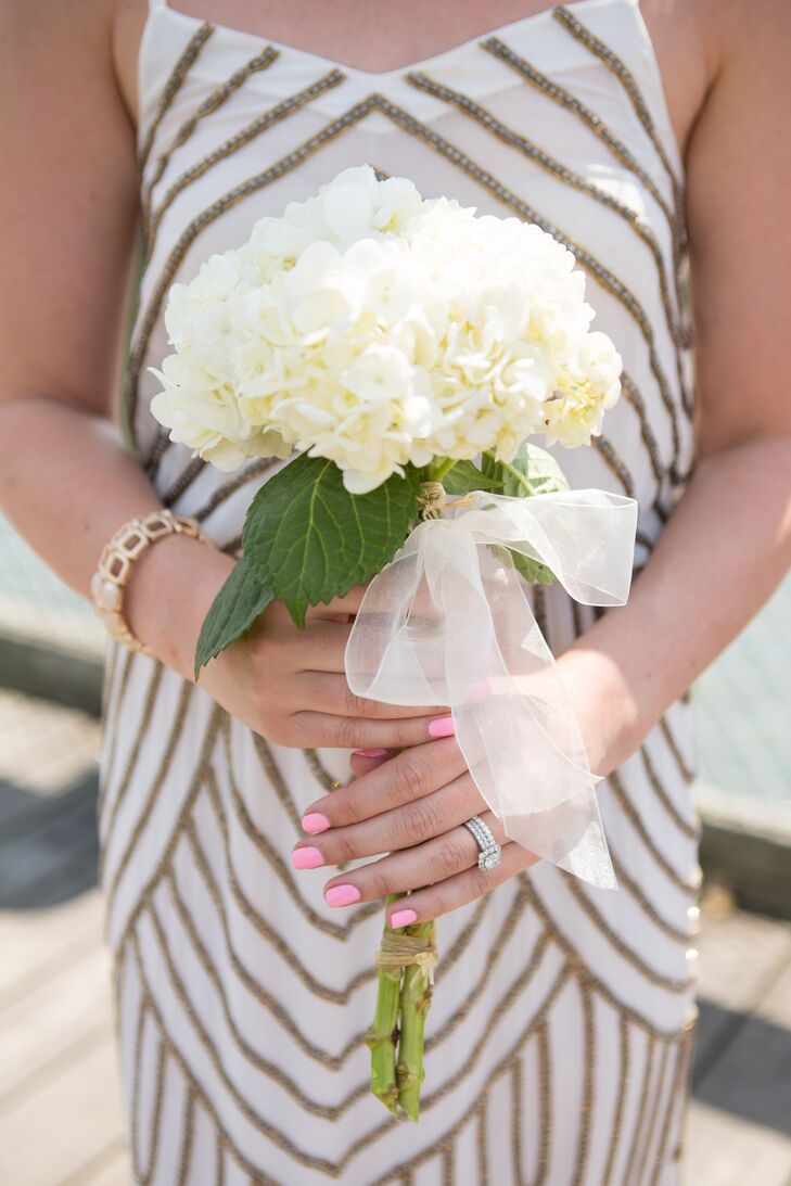 The bridesmaids carried two stems of white hydrangeas tied together with sheer ivory ribbon. The bride carried light pink, peach and ivory roses tied with a similar ivory ribbon to match the bridesmaid dresses.