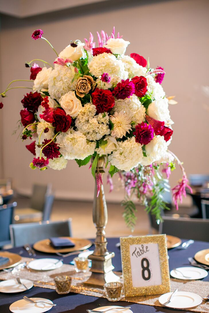 The couple's florist, Exquisite Petals, was able to interpret their design concept of Great Gatsby, bohemian, asymmetrical and romantic. The tall table floral arrangements featured striking displays of wine, fuschia, white and gold flowers such as dahlias, hydrangea and roses.