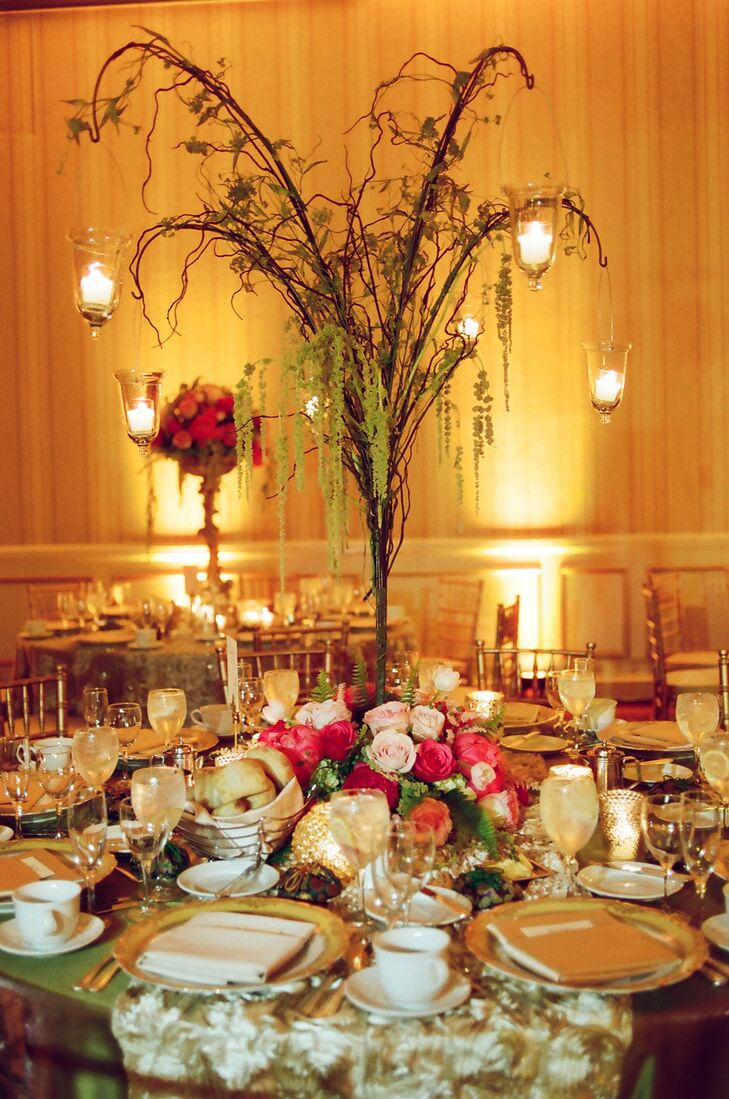 Tall tree-branch centerpieces give the tables a dreamy, romantic, forest-like atmosphere. Hanging tealight candles lend an ethereal feel.