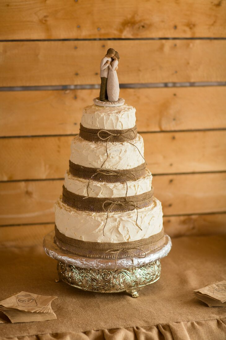 The four-tier wedding cake covered with white frosting had burlap wrapped around the bottom of each tier. A Willow Tree figurine topper perfectly matched the style of the cake.
