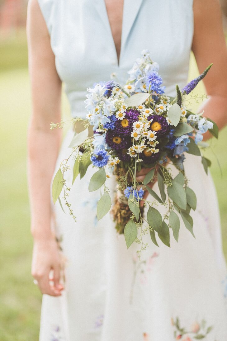 The florists at Beautiful Bloom Events were the masterminds behind all the wedding flowers. Taking the couple's low-key vision into heart, they created bountiful bundles of fresh-picked wildflowers in shades of brilliant blue and white. The loosely arranged bouquets perfectly captured the day's casual, rustic theme.