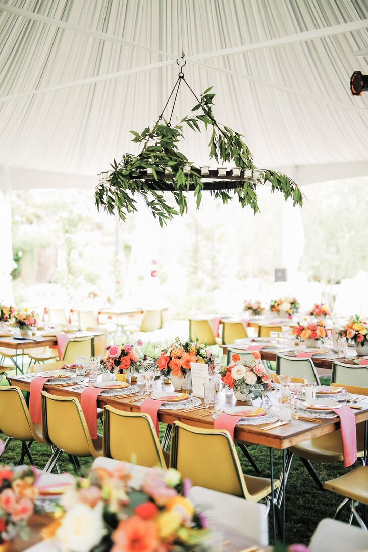 Under a white canopy the couple matched long, light wood tables with bright, contemporary-style chairs. Above, a chandelier was bedecked with greenery.