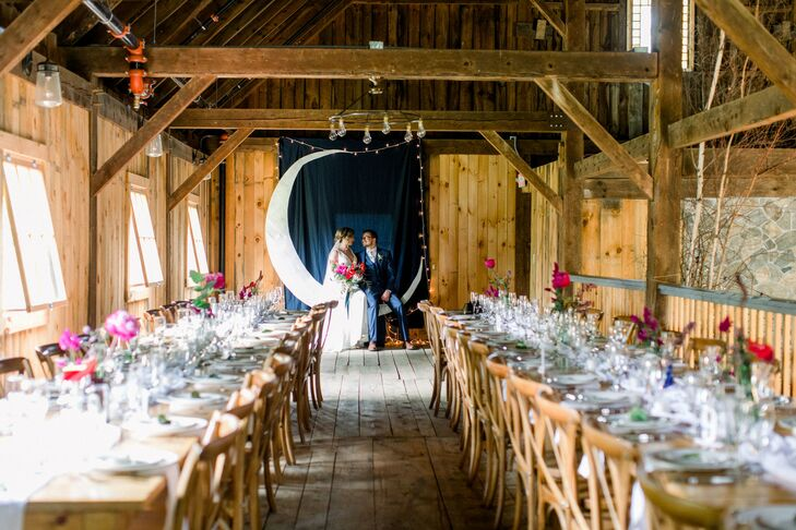 Wood Barn Reception with Rustic Dining Tables and Moon-Shaped Backdrop